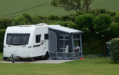 Touring caravan with awning on camping pitch at Looe Country Park